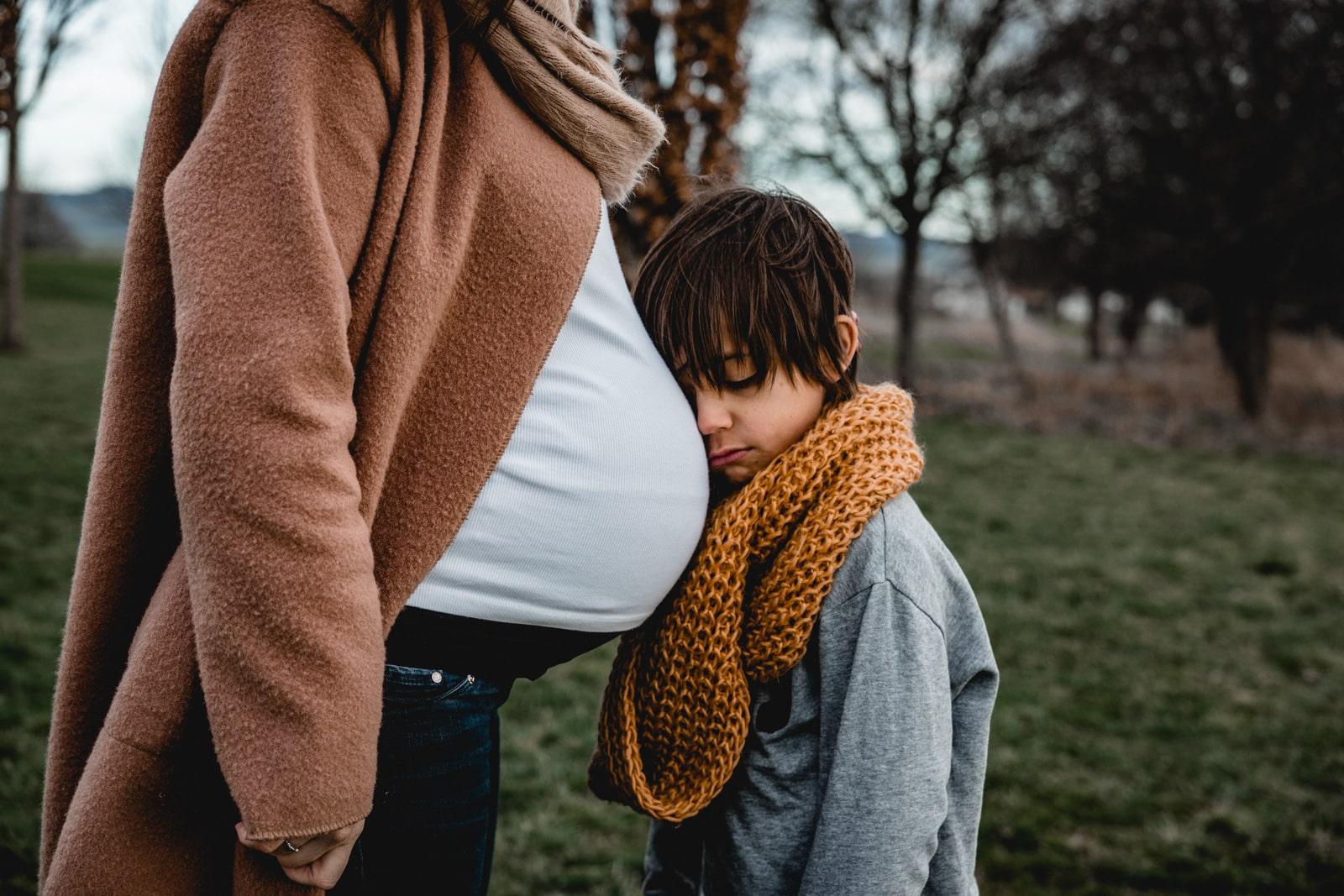 Kind lehnt an den Babybauch der Mama mit Kopf an