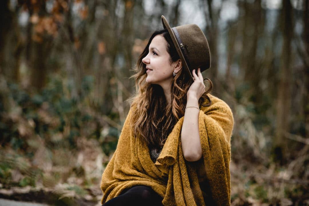 Frau sitzt mit Hut und ockerfarbener strickjacke im wald