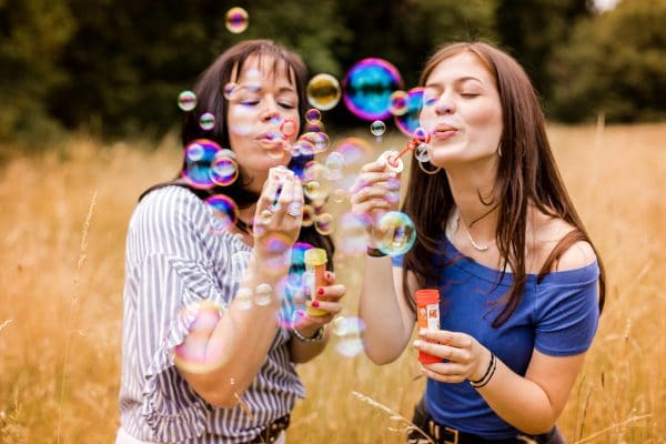 Zwei Frauen blasen Seifenblasen in einem Grasfeld auf der Rosenhoehe in Darmstadt