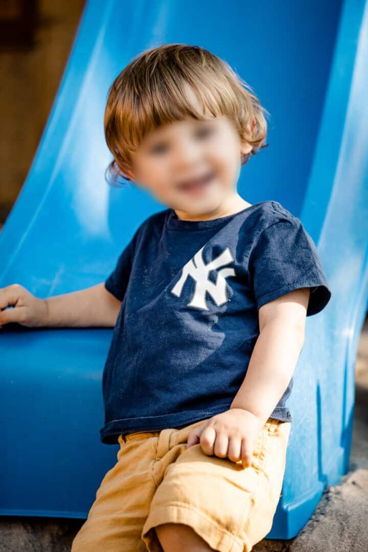Ein kleiner Junge im blauen T-Shirt lehnt an eine Rutsche und lacht in die Kamera