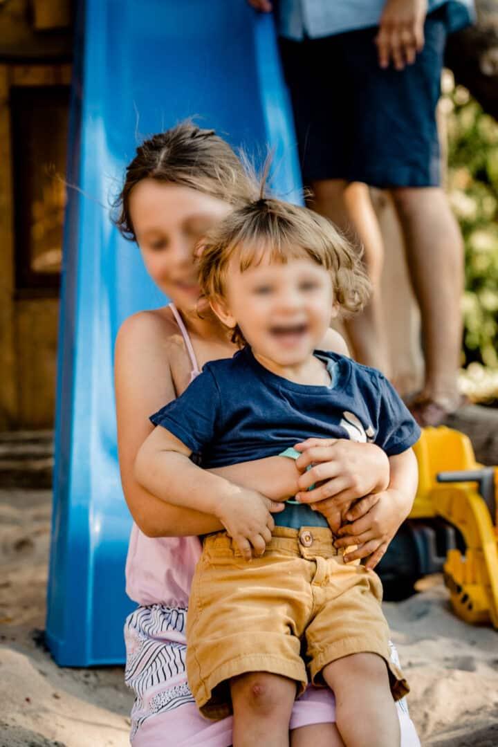 Zwei Kinder rutschen zusammen die Rutsche runter im Sommer