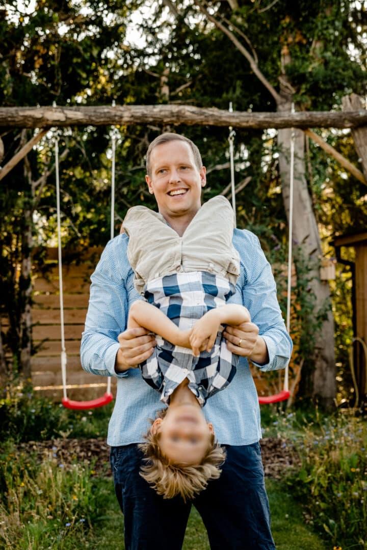 Sohn hängt am hals vom Vater Kopfüber