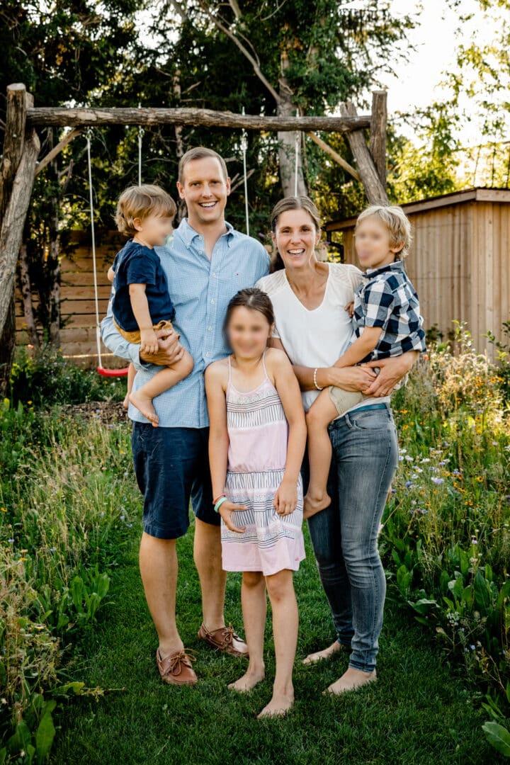 Familie steht in der Natur und lacht in die Kamera
