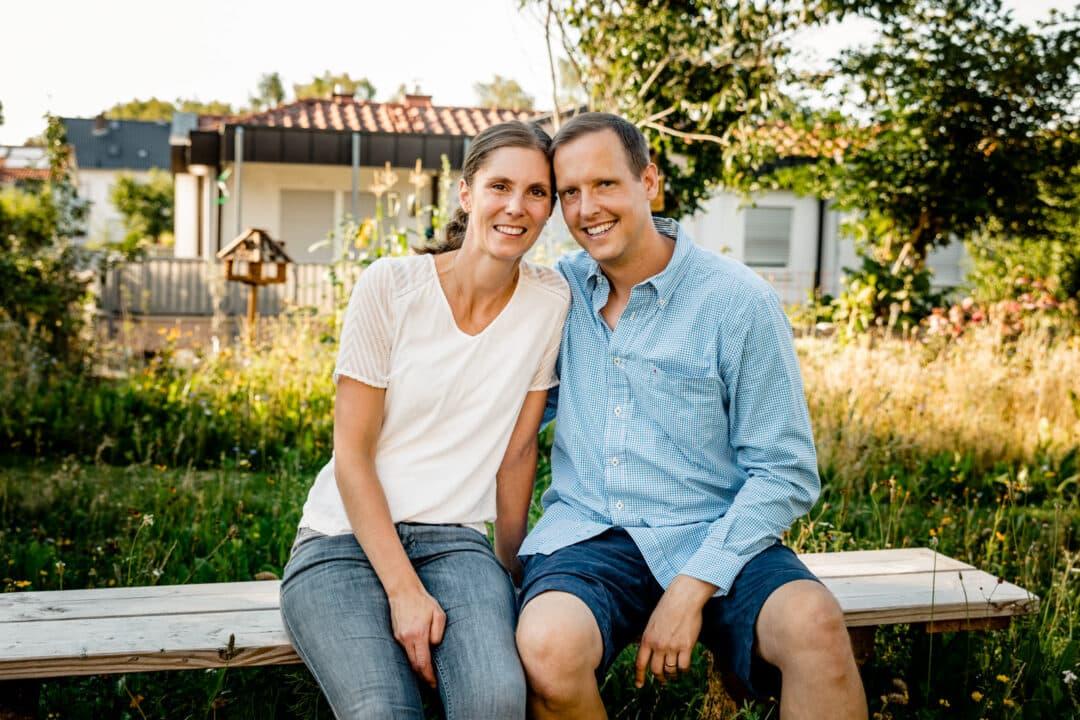 Mann und Frau sitzen im Sommer auf einer Bank und lachen