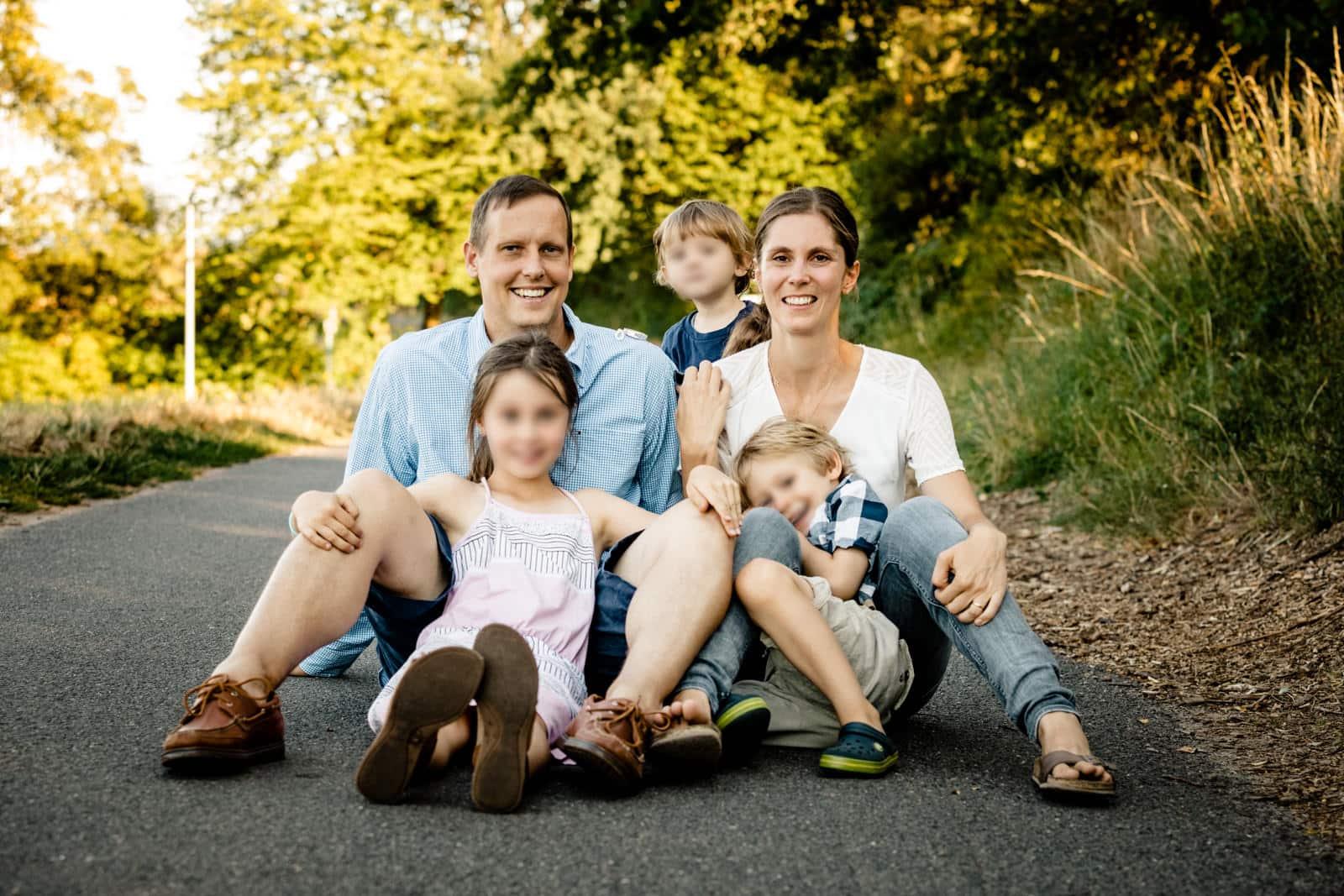 Familie sitzt zu fünft auf einem betonierten Weg in der Natur mit Sonne im Hintergrund