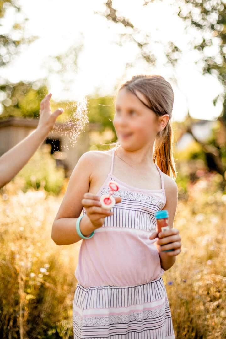 Mädchen schaut zu einer zerplatzenden Seifenblase