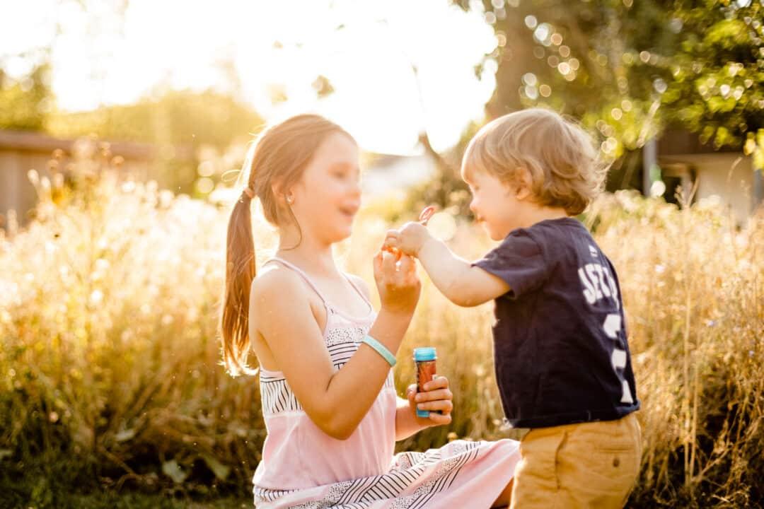 Zwei Kinder spielen draussen mit Gegenlicht und Seifenblasen