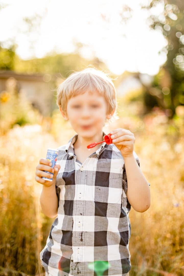 Junge bläst Seifenblase mit untergehender Sonne