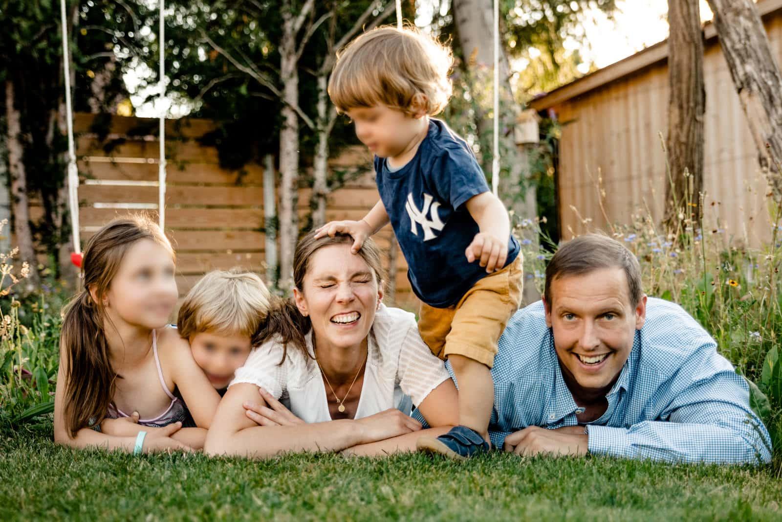Eine Familie liegt auf dem Rasen und lacht in die Kamera während der Sohn über alle drüber steigt