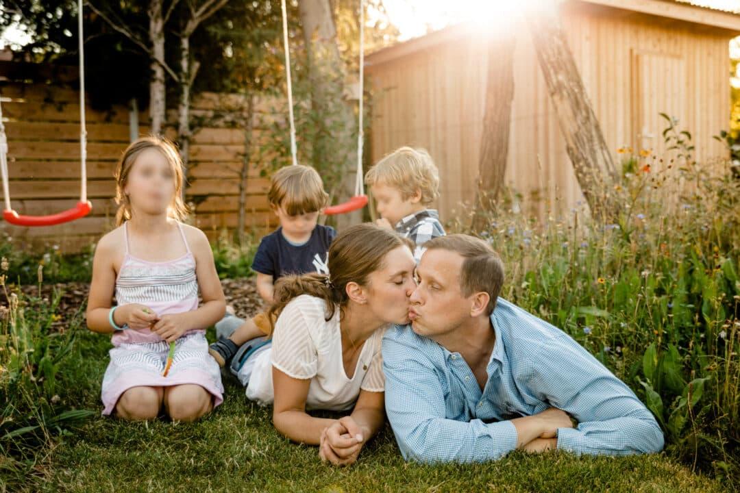Eltern lieben auf dem Rasen und Küssen sich während die Kinder Süssigkeiten essen. Sonnenschein