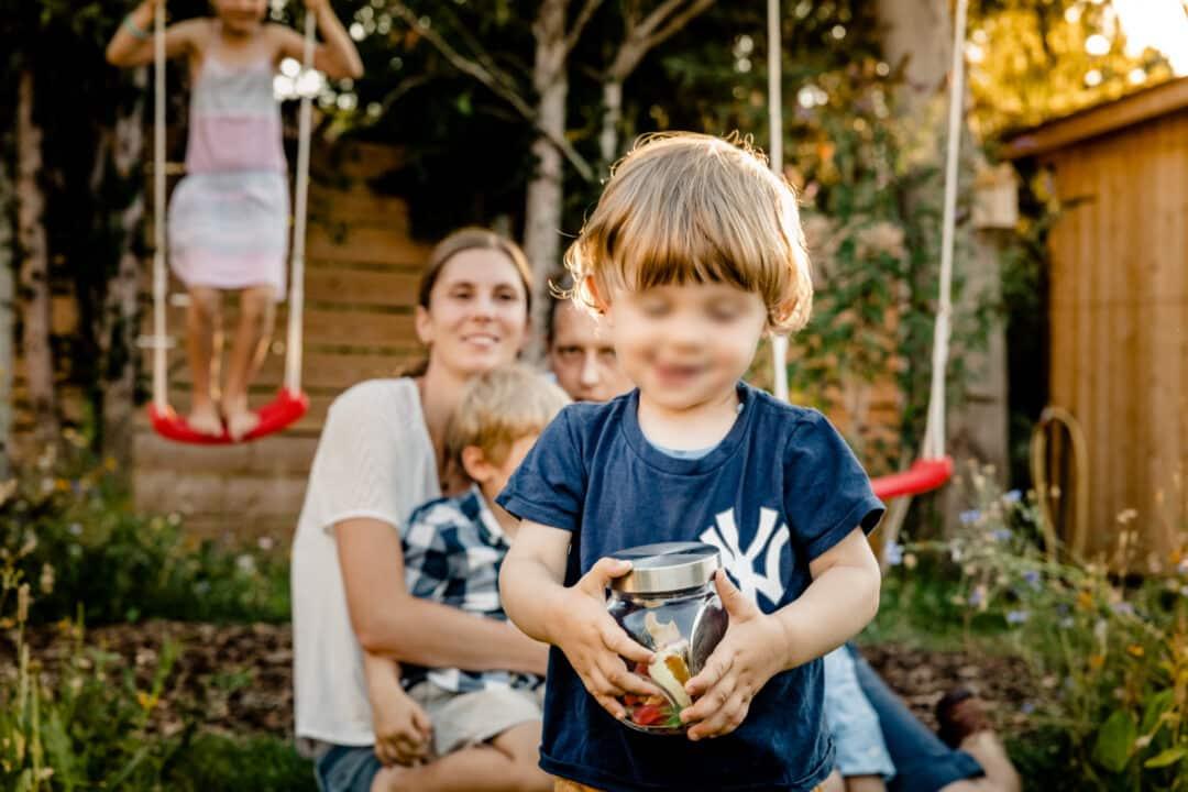 Sohn klaut Süssigkeitenglas während eines Fotoshootings mit der Familie im Garten