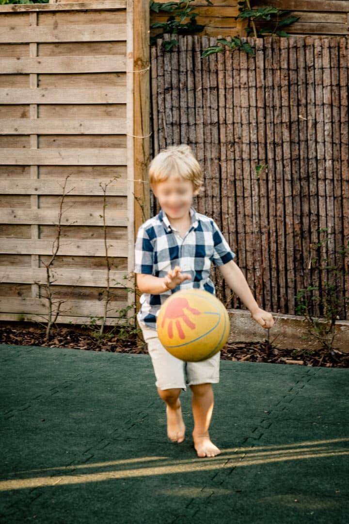 Junge spielt Basketball im Garten im Sommer