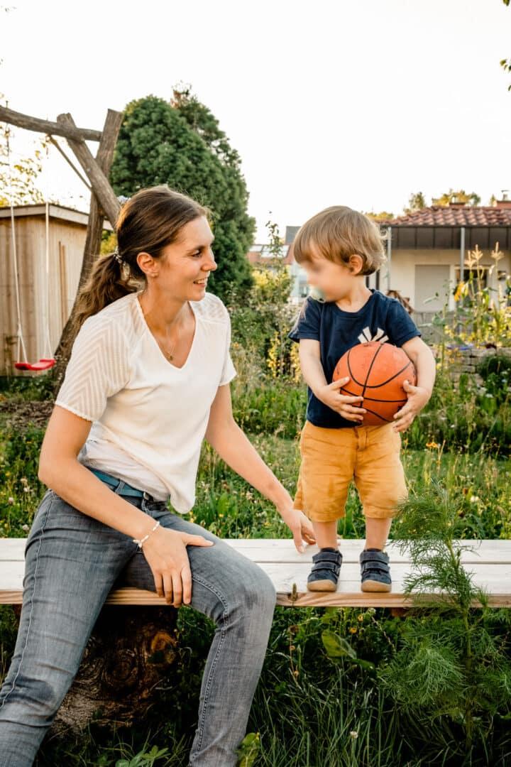 Mutter sitzt auf Bank und neben ihr steht ihr Sohn mit einem Basketball in der Hand und schauen sich an