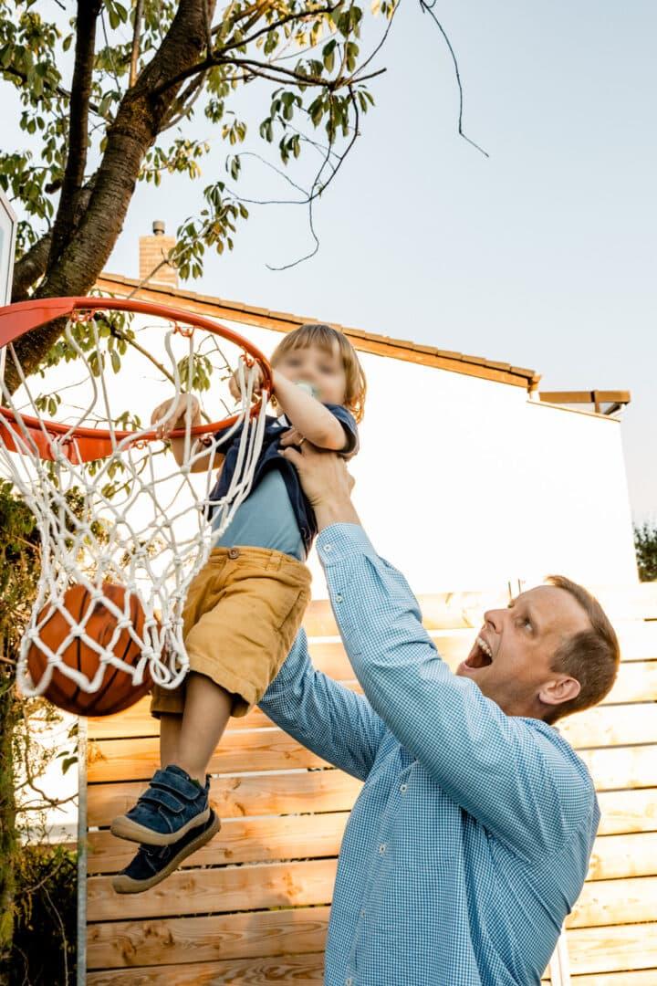Vater hebt seinen Sohn zum Basketballkorb hoch zum Ball hinweinwerfen