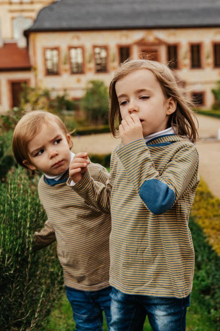 Ein Mädchen riecht an einem Rosmarinbusch und ihr Bruder schaut zu