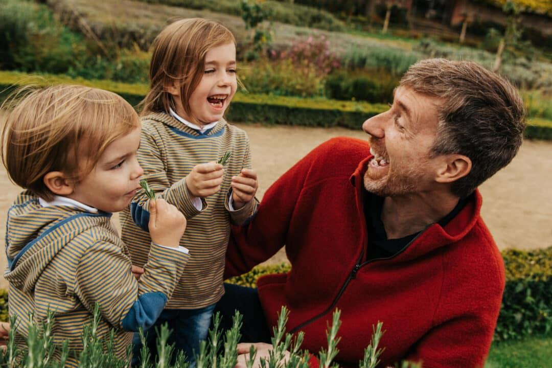 Ein Vater lacht mit seinen zwei Kindern im Park am Rosmarinbusch