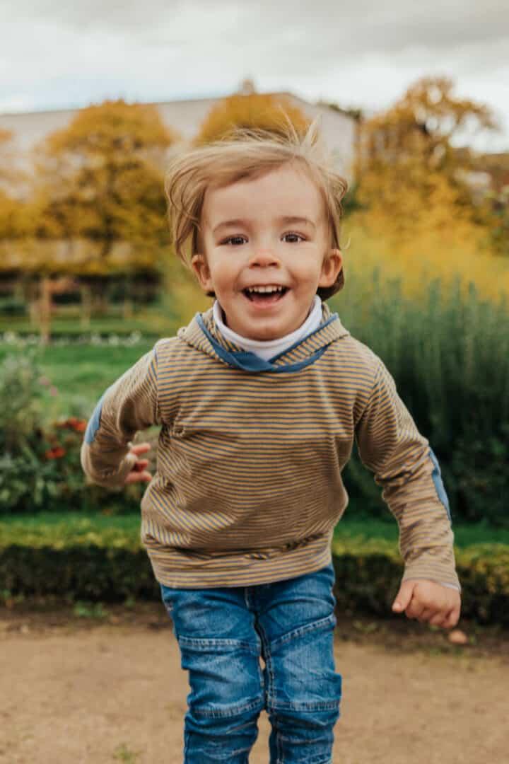 Ein kleiner Junge springt hoch und lacht in die Fotokamera