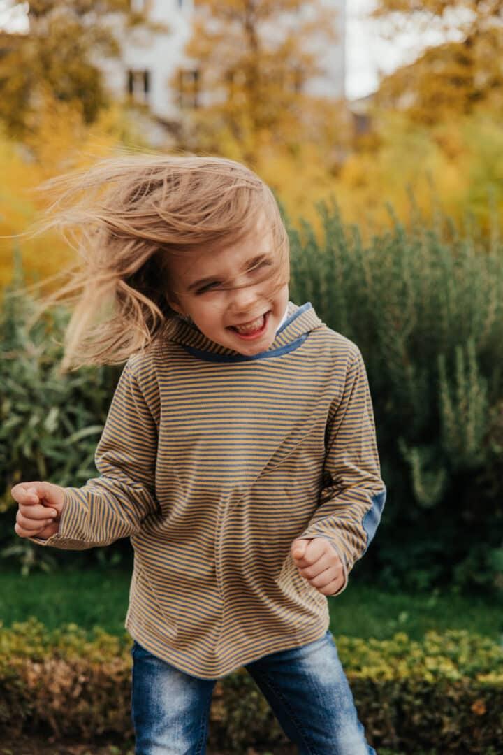 Ein kleines Mädchen lacht und schüttelt ihr Haar wild