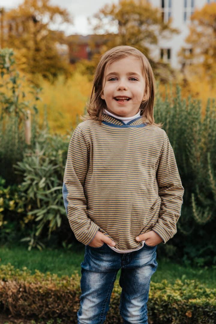 Ein kleines Mädchen im Park posed für die Kamera mit den Händen in der Hosentasche