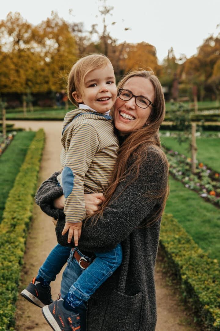 Eine Mutter hat ihren Sohn auf dem Arm und lachen in die Kamera