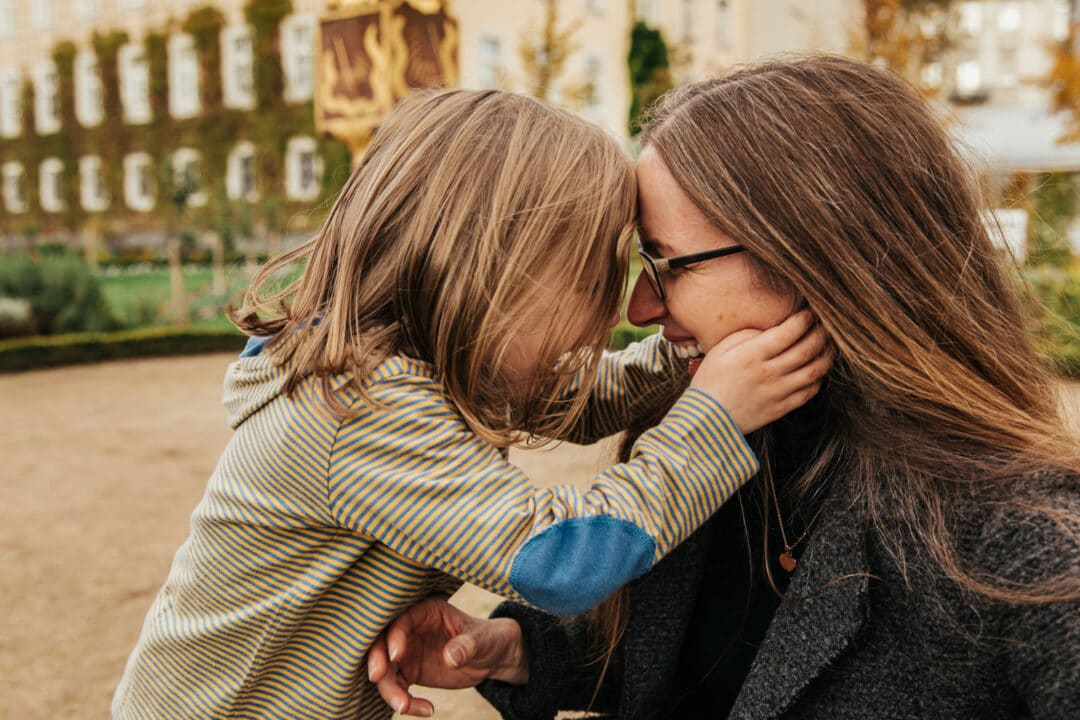 Eine Mutter und ihre Tochter halten ihre Köpfe aneinander und lachen