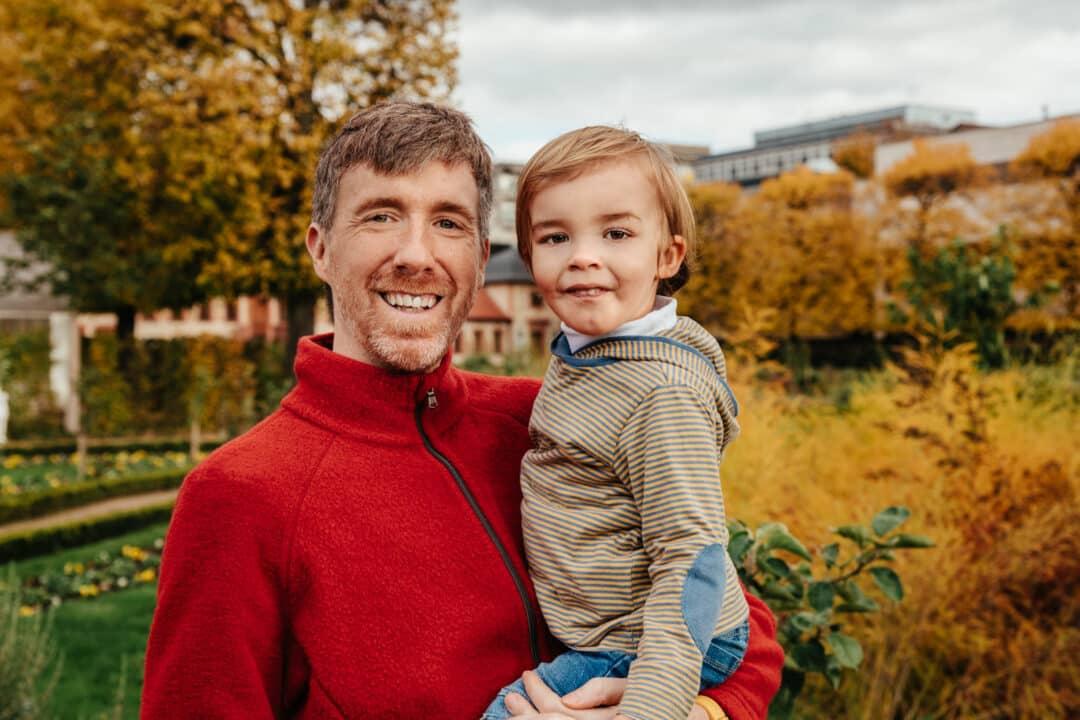 Ein Vater hat seinen Sohn auf dem Arm bei Familienfotos im Park