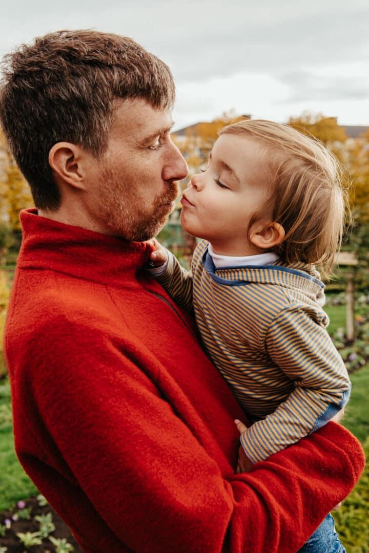 Ein Junge auf dem Arm seines Vaters küsst ihn