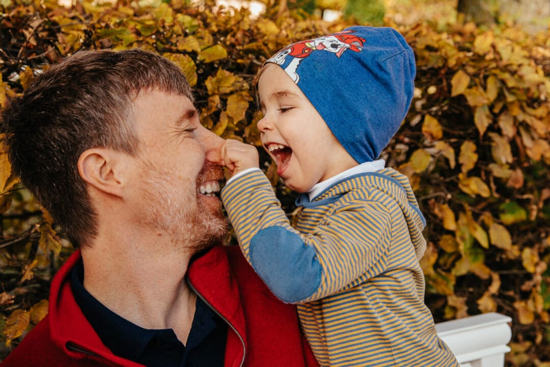 Ein Junge lacht und zwickt seinem Vater in die Nase