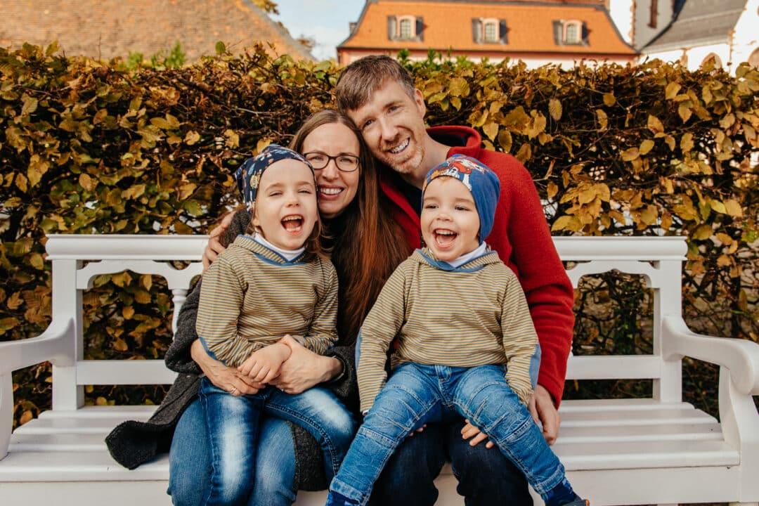 Eine vierer Familie sitzt auf einer Parkbank und lacht in die Kamera