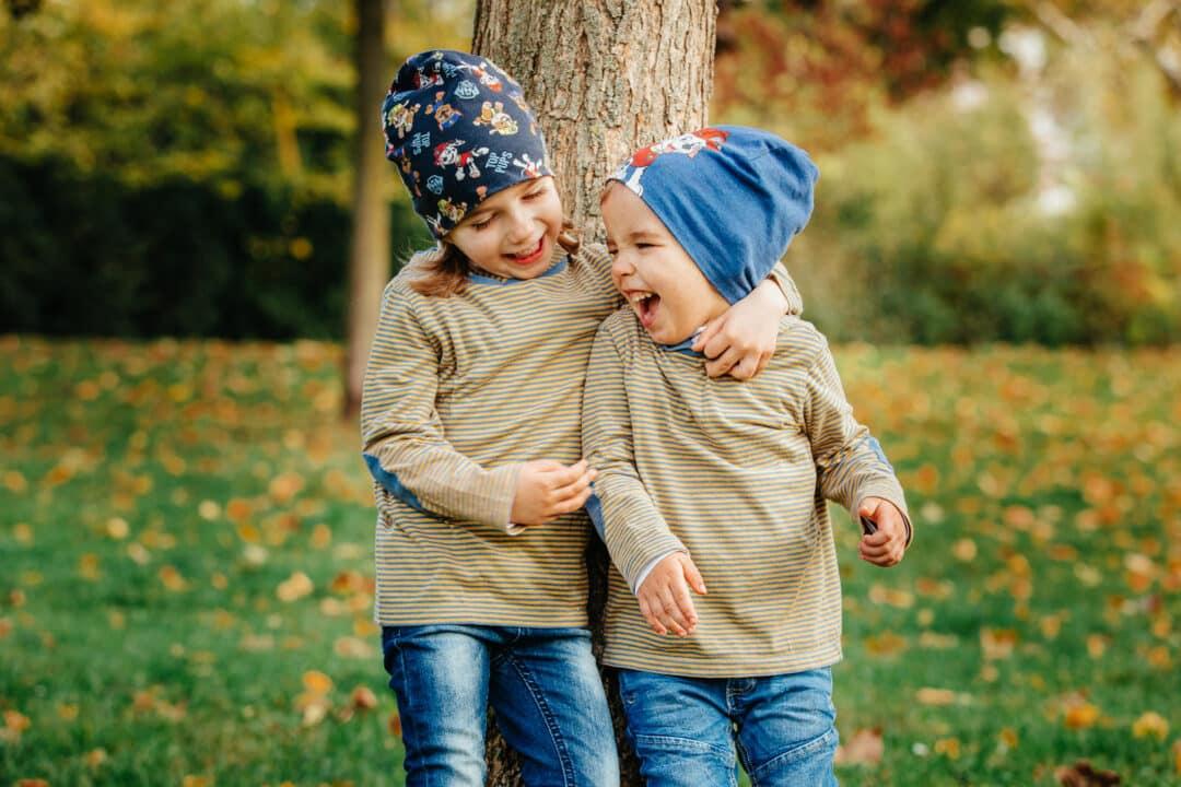 Zwei Geschwisterkinder halten sich im Arm und lachen im Park