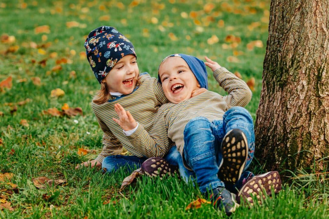 Zwei Geschwisterkinder liegen auf dem Rasen und lachen