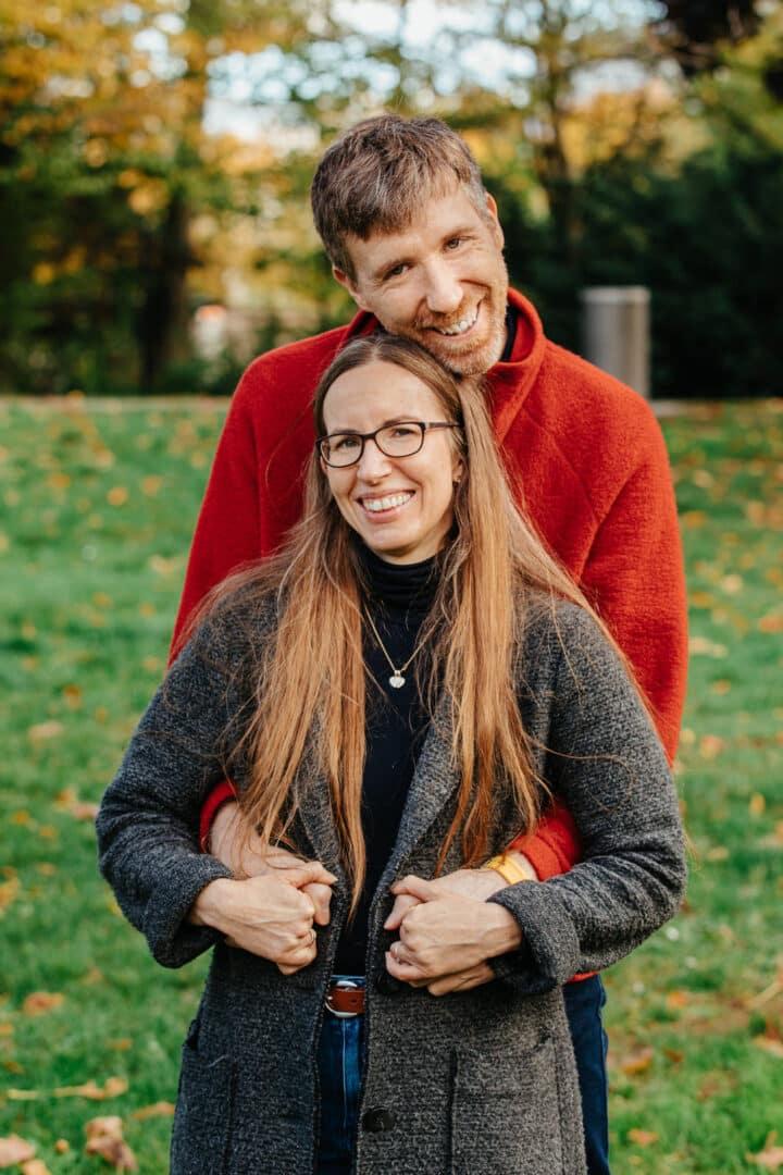 Vater und Mutter lachen in die Kamera während er sie im Arm hält