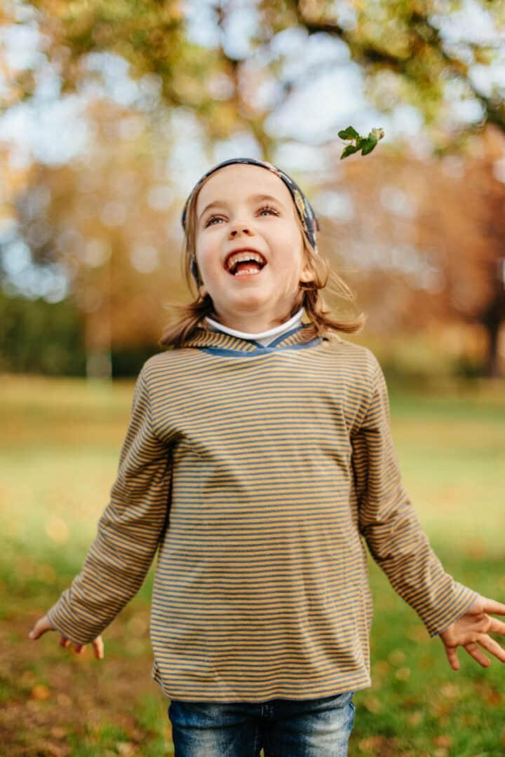 Ein kleines Mädchen wirft Herbstlaub nach oben