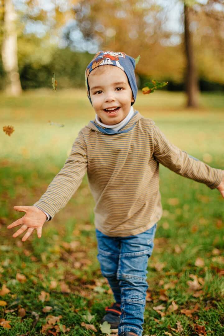 Ein kleiner Junge wirft lachend Herbstlaub nach oben