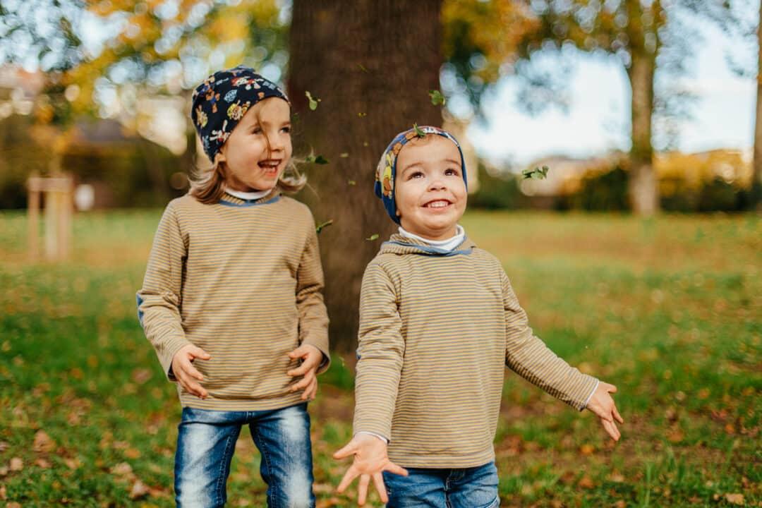 Zwei Geschwister werfen Herbstlaub nach oben