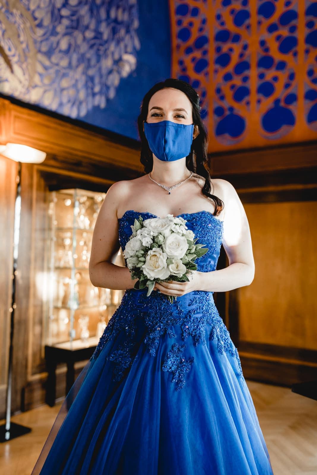 Braut mit blauer Mund-Nase Maske lacht in Kamera