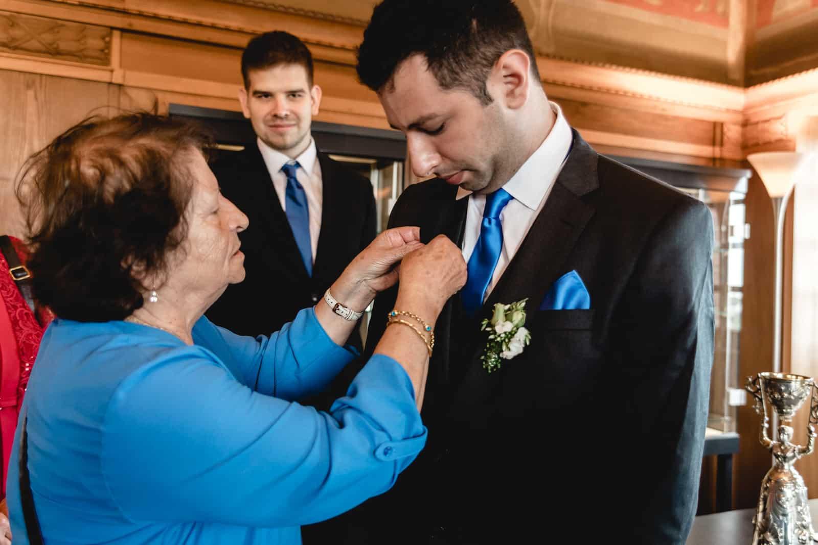 Brautmutter steckt ihrem Sohn eine Schleife an