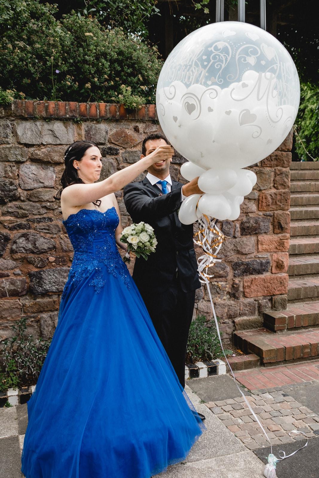 Brautpaar zersticht einen Luftballon und viele kleine weiße Herzluftballons fliegen weg