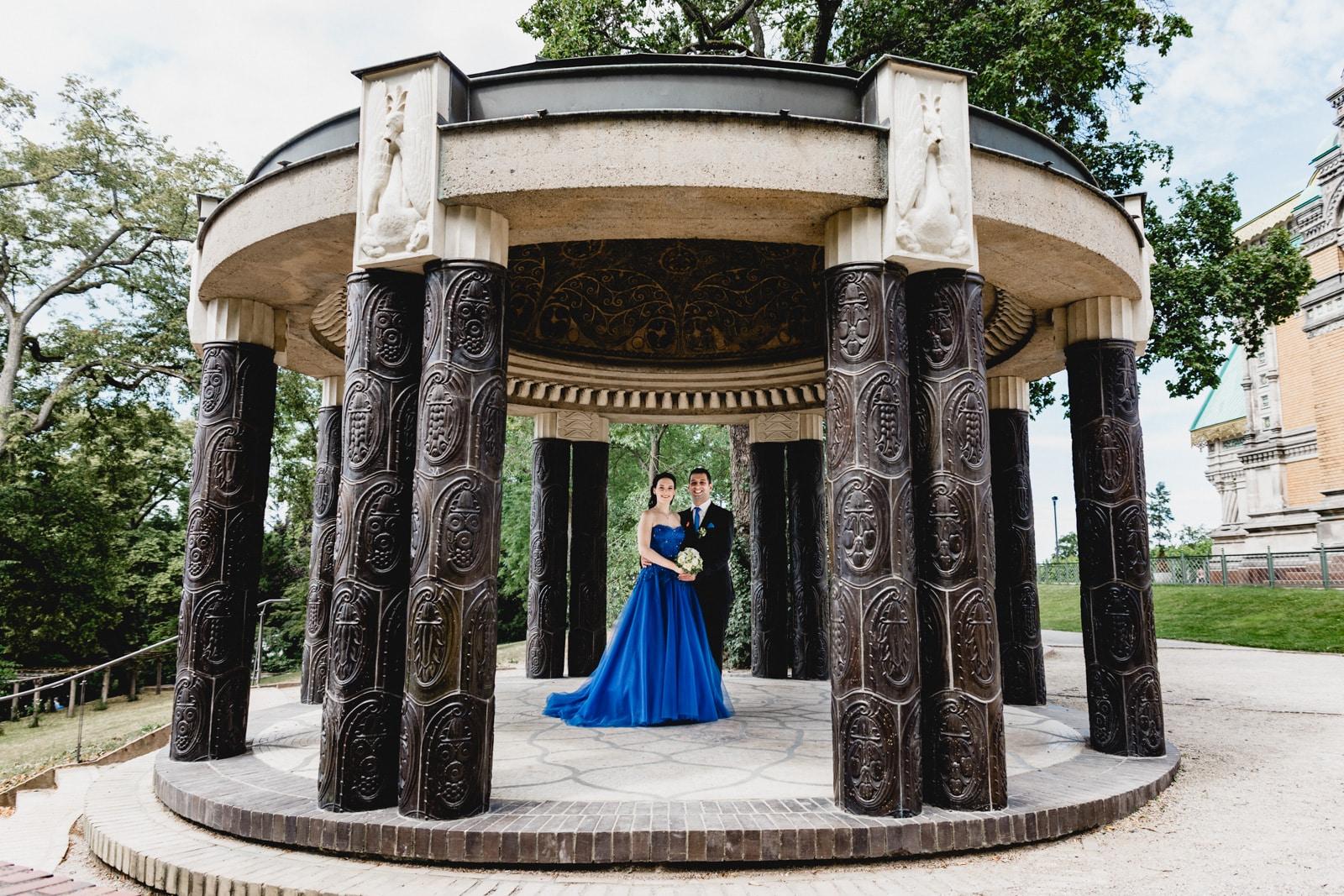 Bräutigam und Bräutigam lachen in die Kamera und stehen unter einem Pavillion auf der Mathildenhöhe Darmstadt
