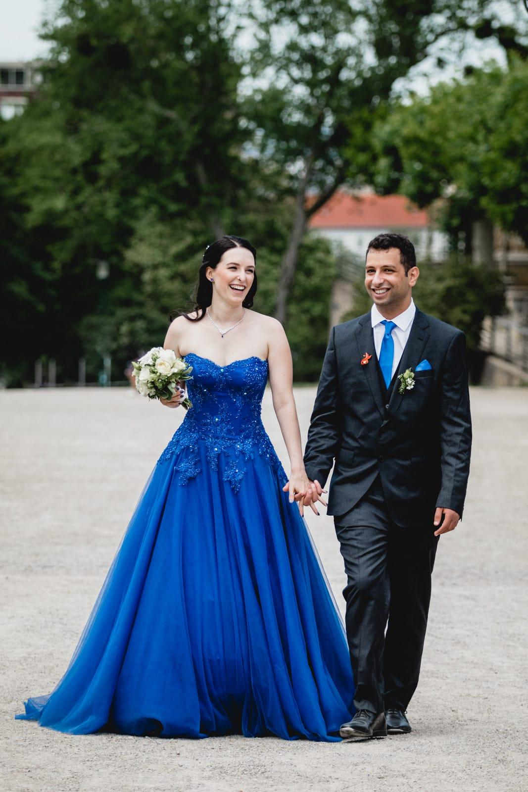 Eine Braut im blauen Brautkleid läuft zusammen mit ihrem Mann Hand in Hand auf der Mathildenhöhe in Darmstadt