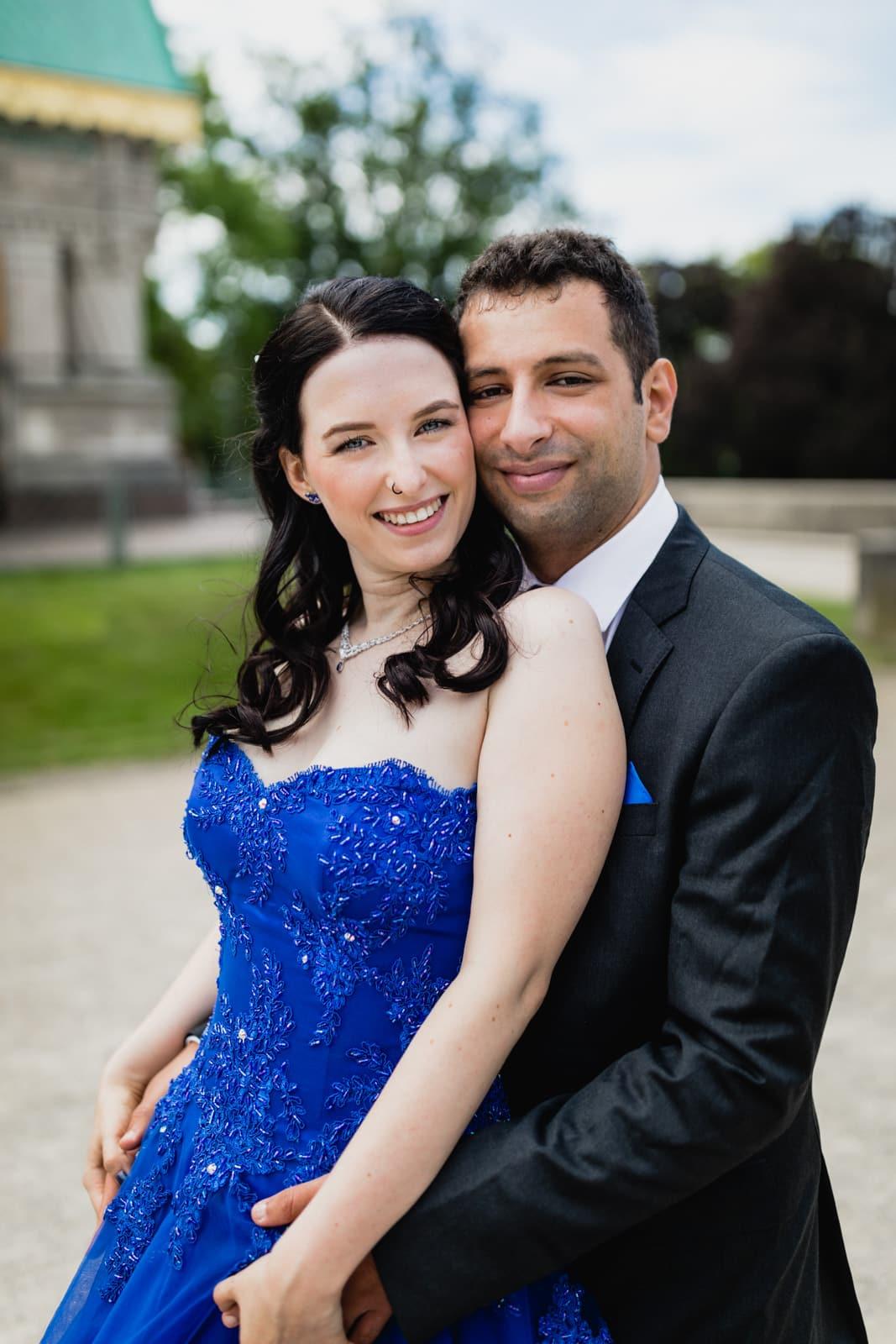 Braut und Bräutigam stehen voreinander angeschmiegt und lachen in die Kamera