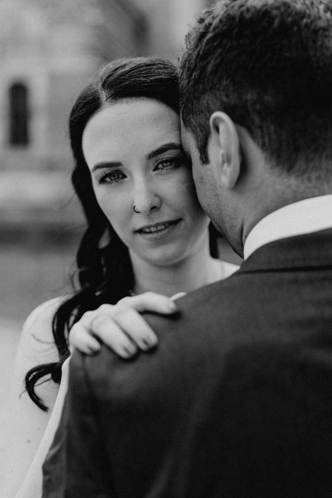 Braut schaut in die Kamera angeschmiegt an den Kopf ihres Mannes