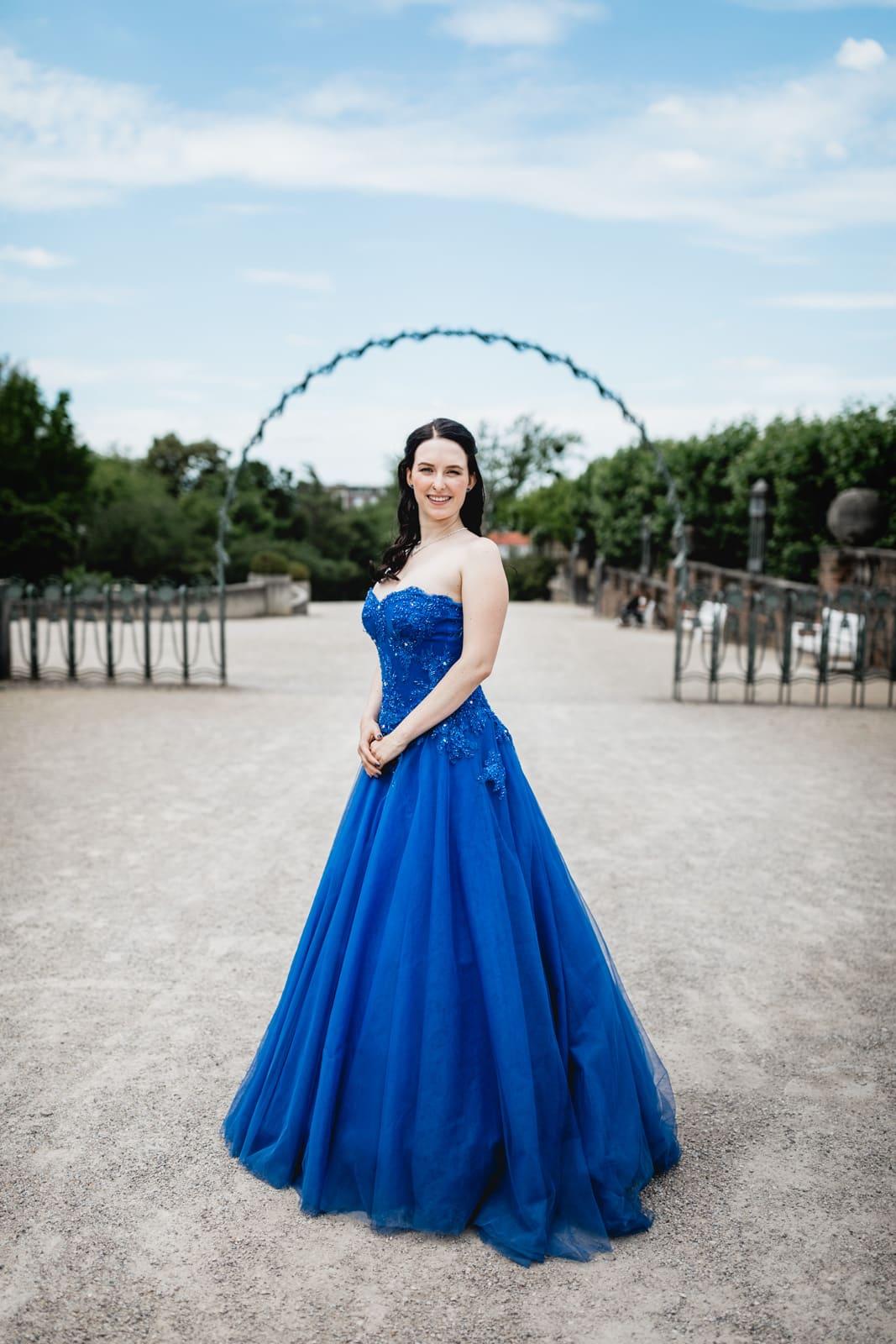 Braut im blauen Brautkleid auf der Mathildenhöhe Darmstadt steht unter Bogen