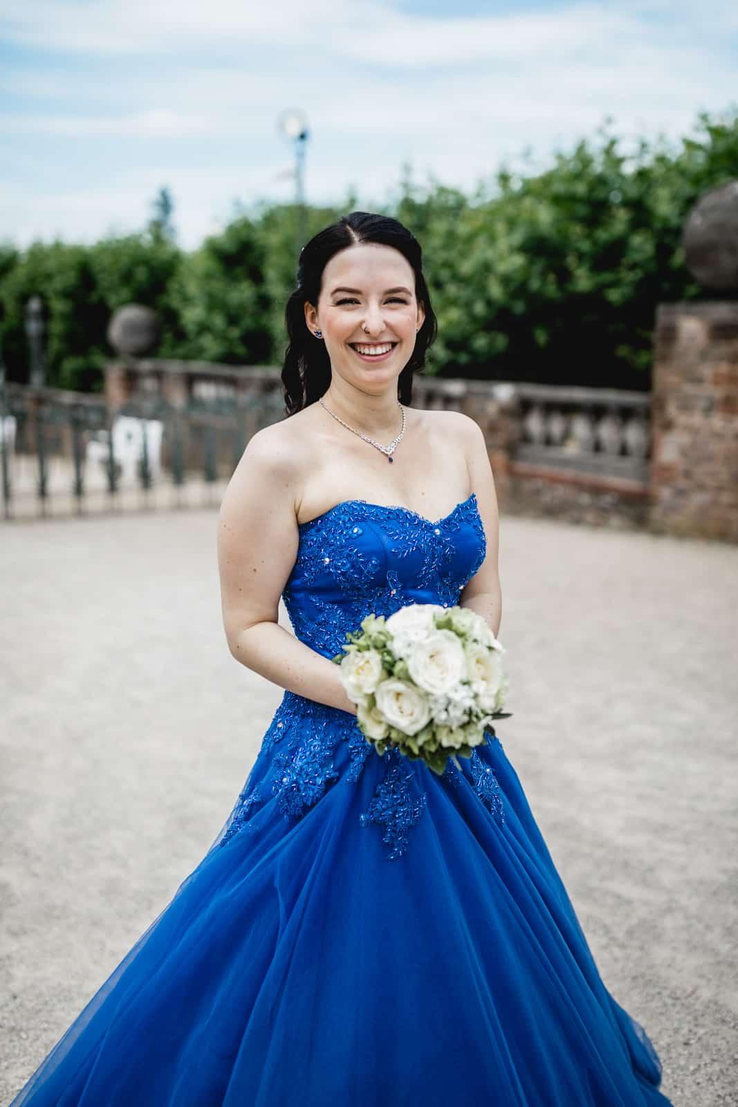 Braut im blauen Brautkleid auf der Mathildenhöhe Darmstadt lacht in die Kamera
