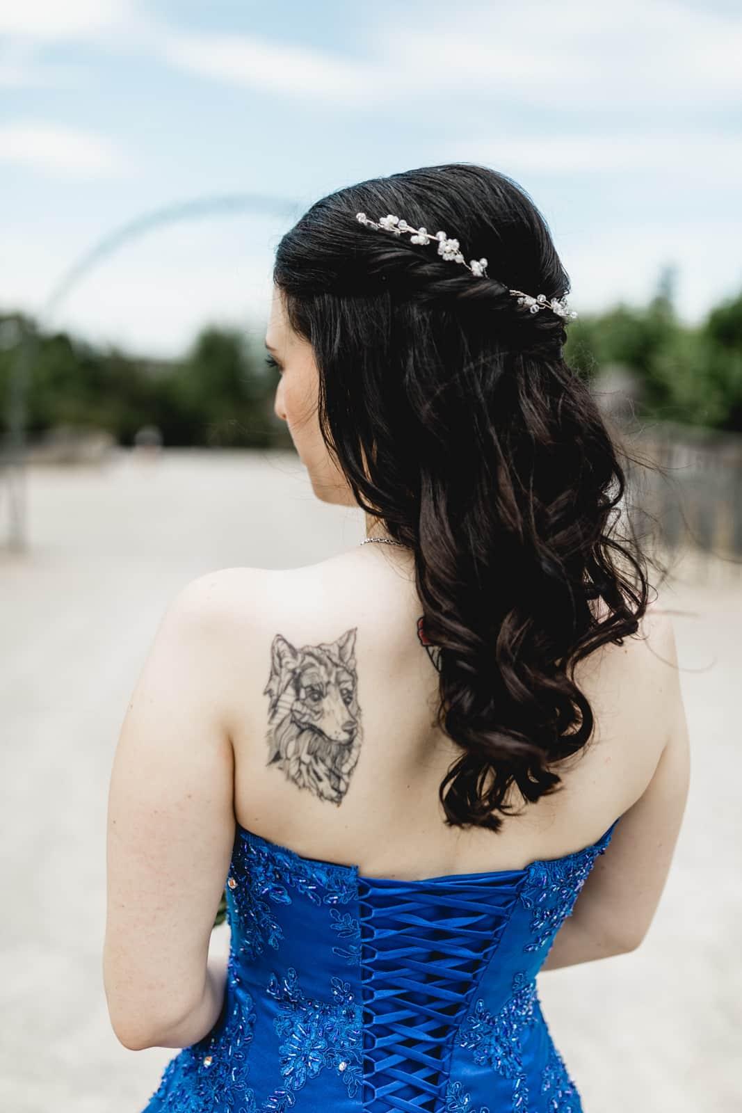 Braut im blauen Brautkleid von hinten mit Wolftattoo auf der Schulter auf der Mathildenhöhe in Darmstadt