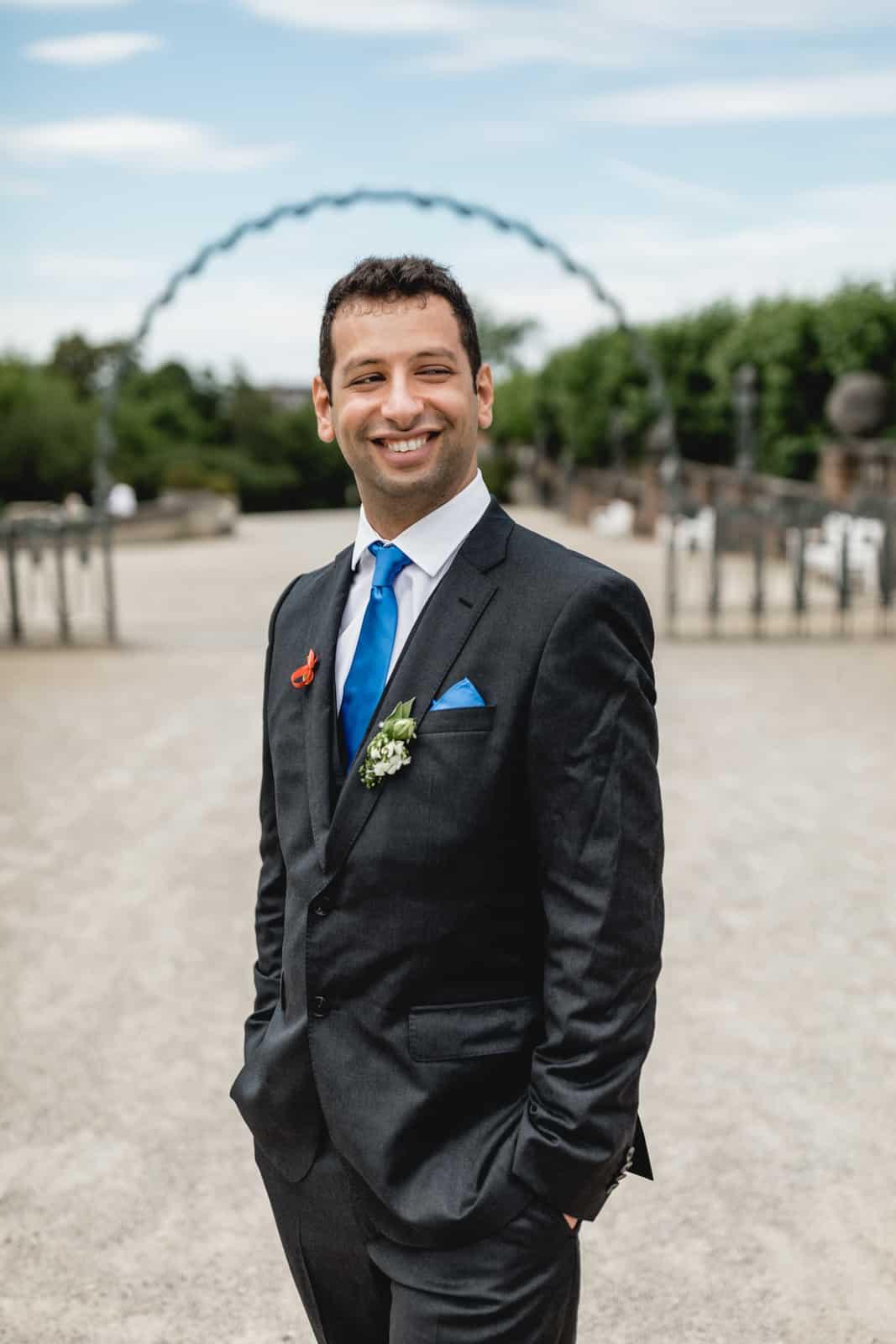 Bräutigam lacht und hat Hände ich den Taschen während seines Portraitshootings auf der Mathildenhöhe in Darmstadt