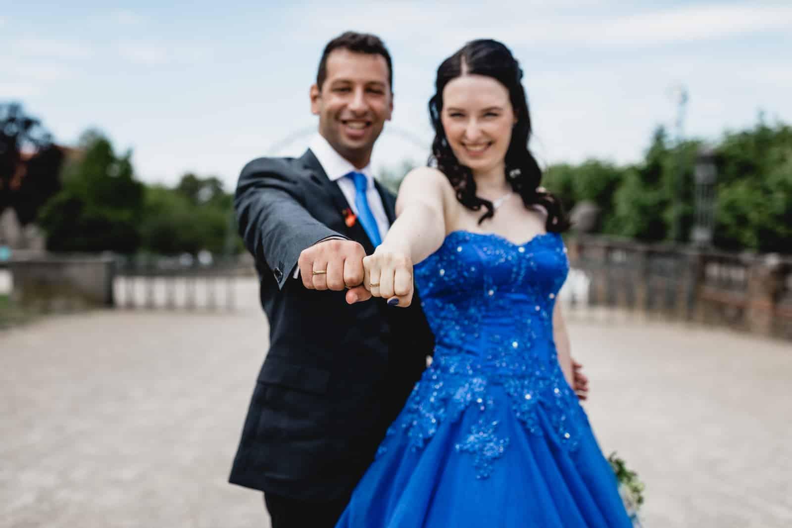 Braut in blau und ihr Mann zeigen ihre Ringe in die Kamera auf der Mathildenhöhe Darmstadt