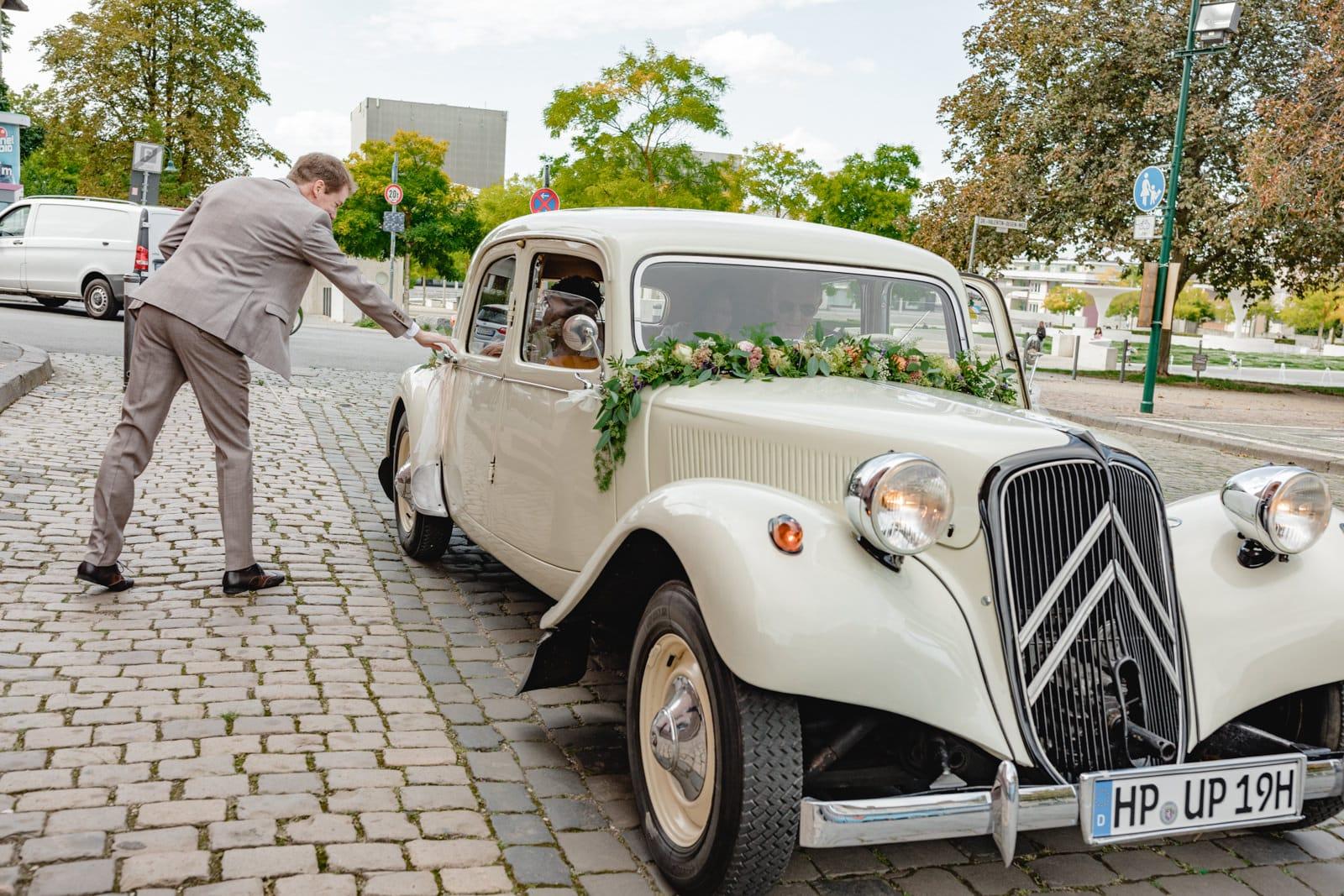 Bräutigam öffnet die Tür zum Oldtimer Brautauto vor der St. Ludwig Kirche in Darmstadt.