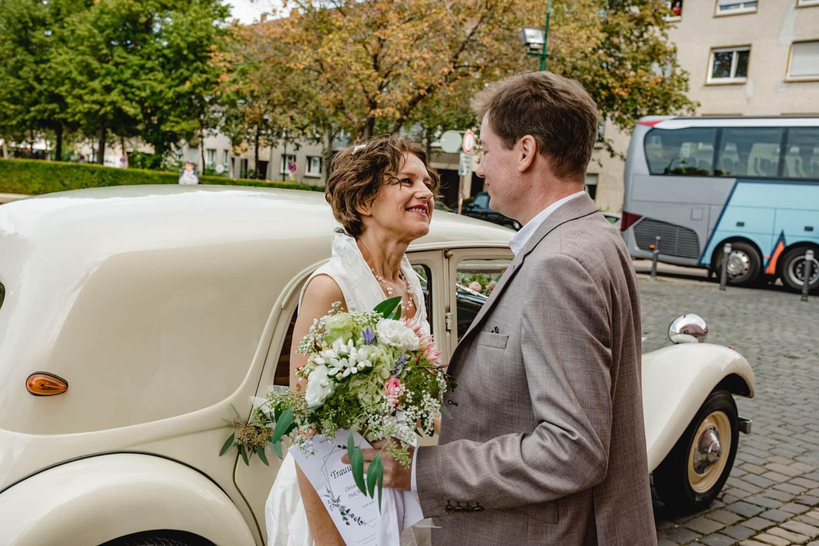 Brautpaar sieht sich das erste Mal nachdem die Braut aus einem Oldtimer ausgestiegen ist an der St. Ludwig Kirche in Darmstadt.