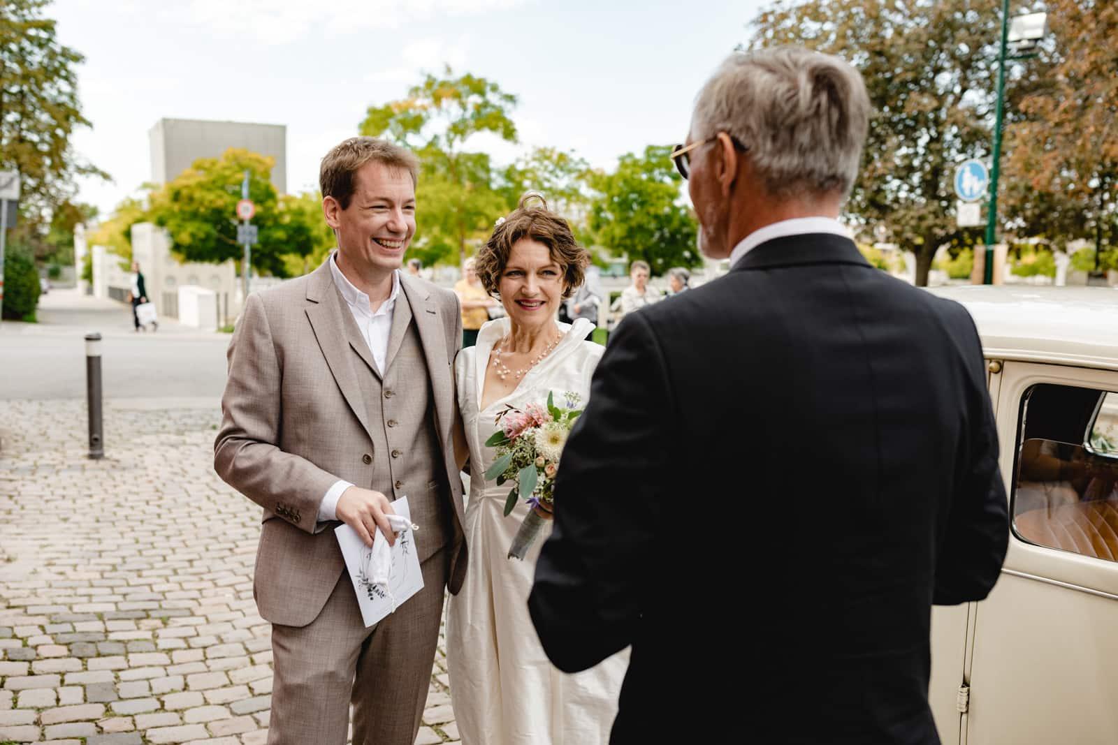 Brautpaar beim Gespräch mit dem Oldtimer Brautauto Fahrer vor der St. Ludwig Kirche in Darmstadt.